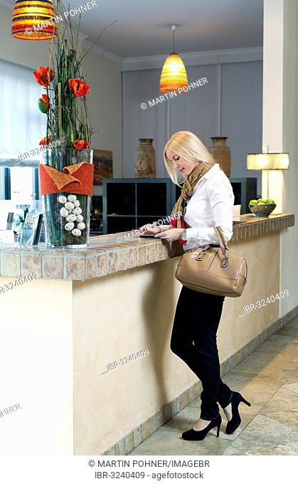Woman standing at the front desk of a hotel