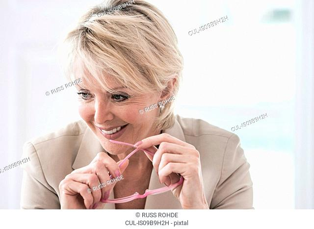 Portrait of business woman holding reading glasses looking away smiling