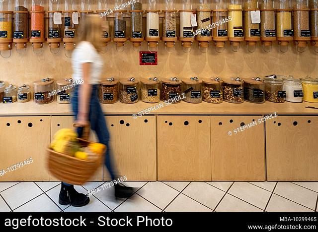 A young customer walks past a shelf with filling containers for grain, detail from an unwrapped shop