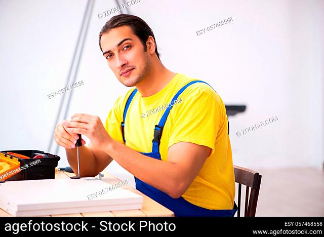 Young male carpenter working at home