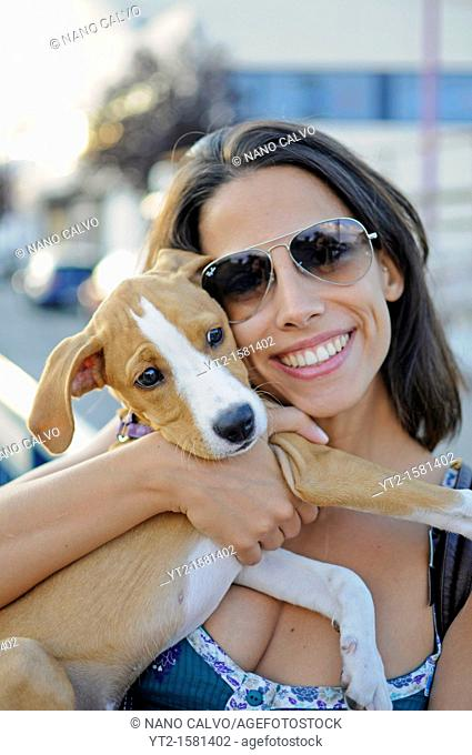 Young attractive spanish girl holding her puppy