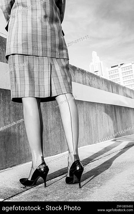 Back view of woman wearing a plaid business suit , Cuban heeled nylon seamed stockings, and vintage crocodile patterned stiletto pumps standing on the top deck...