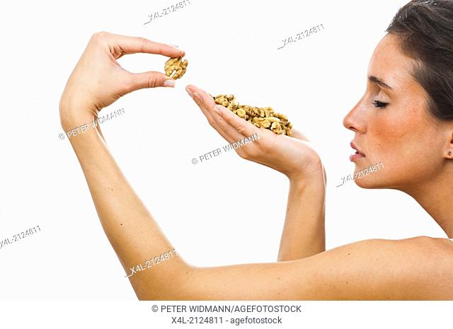 Young woman with a handful walnuts (model-released)