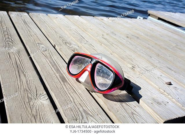 diving goggles on wooden jetty