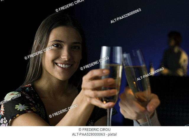 Couple clinking glasses, smiling, cropped view