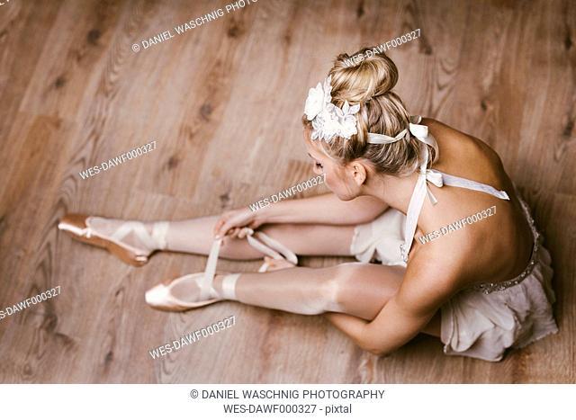 Female ballet dancer sitting on ground