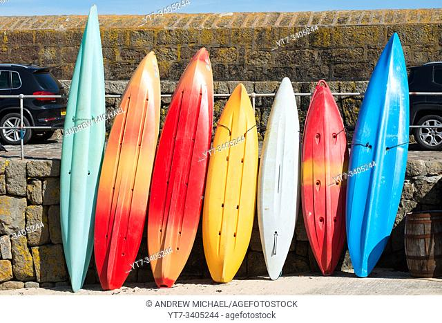 Colourful kayaks lined up at Mousehole in West Cornwall, England, UK