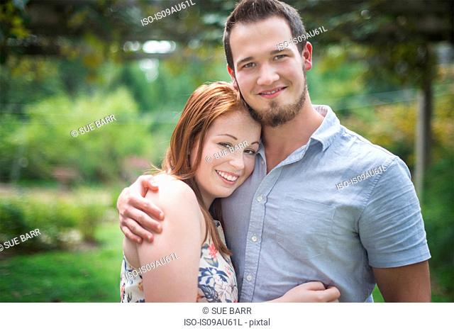 Portrait of couple hugging, looking at camera smiling