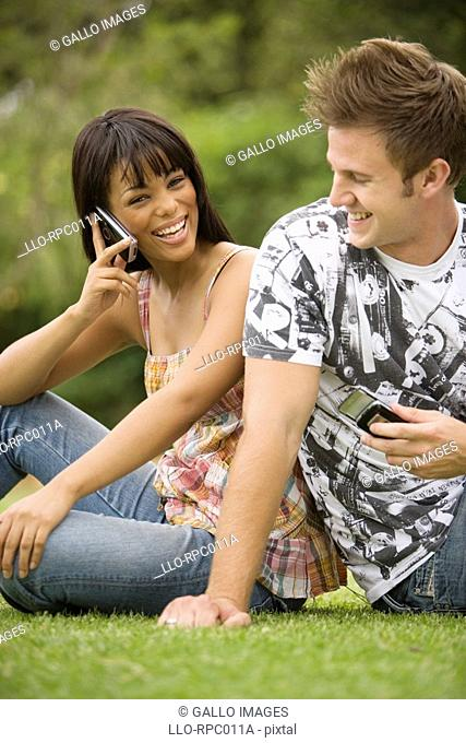 South African teen culture - Young couple sitting back to back on the grass