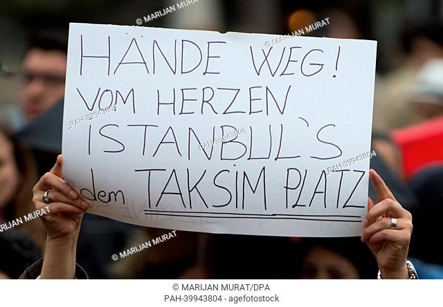 Participant of a demonstration against police violence in Istanbul holds a banner 'Haende weg! vom Herzen Istanbul's dem Taksim Platz' in Stuttgart, Germany