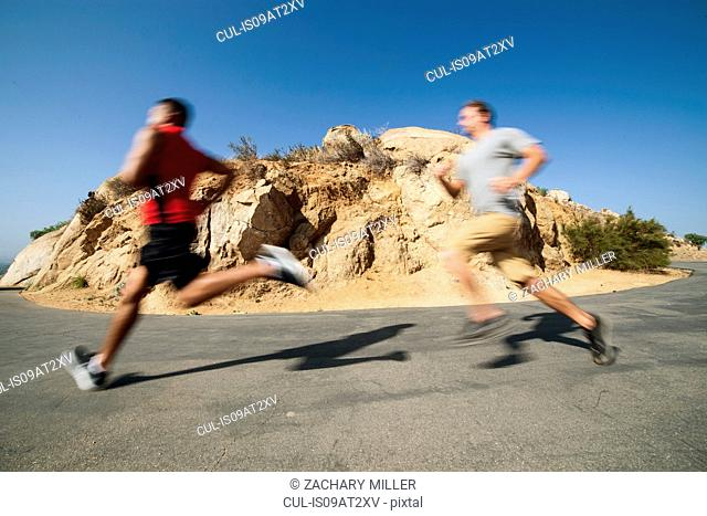 Two male friends, running, outdoors