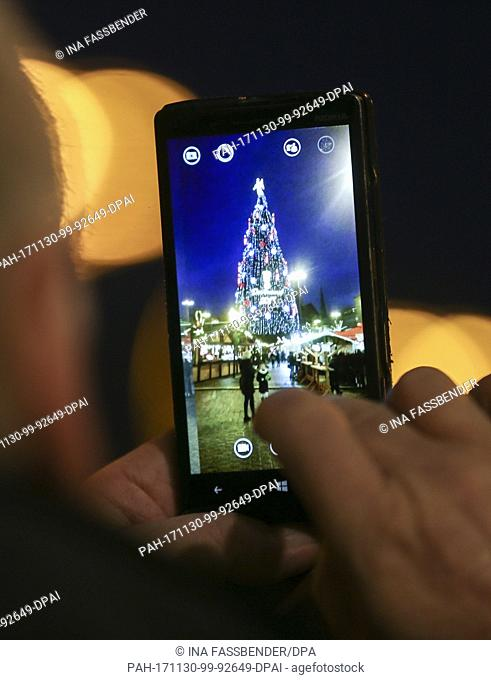 A visitor takes a photo of the according to the organisers biggest Christmas tree in the world at the Christmas market in Dortmund, Germany, 30 November 2017