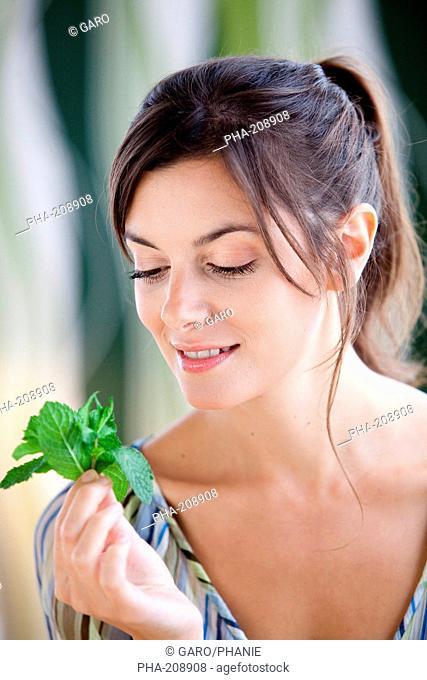 Woman smelling mint leaves Mentha sp