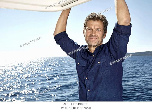 Portrait of relaxed mature man on motor yacht