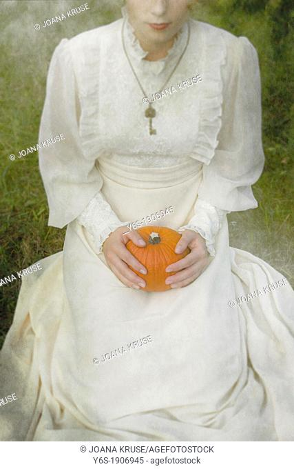 a woman in a victorian dress is sitting on grass and holding a pumpkin on her lap