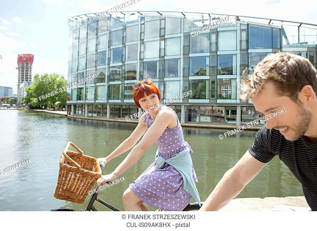 Cyclist couple riding bikes along canal, East London, UK
