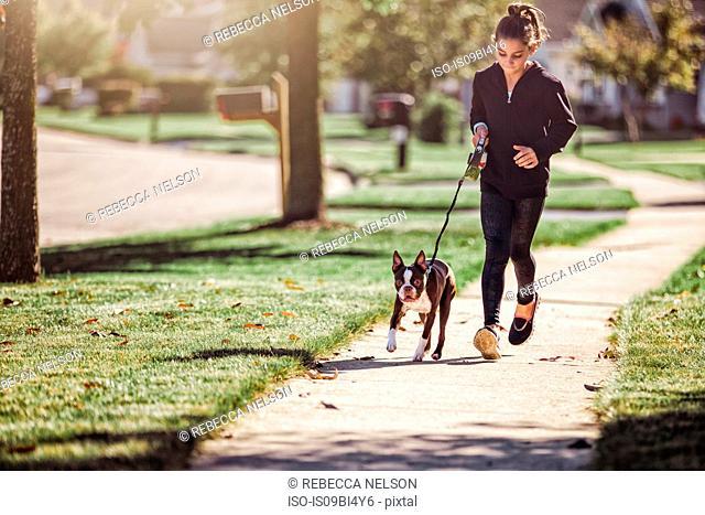 Young girl, walking dog along pathway