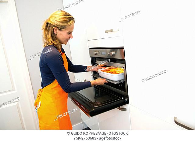 Kaatsheuvel, Netherlands. Mid adult woman placing a feshly made Lasagna dish dinner in her oven
