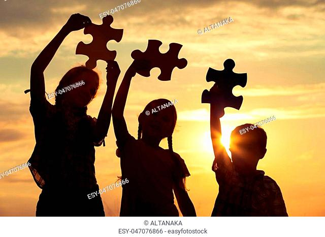 Silhouette of three happy children which playing on the field at the sunset time. They having fun on the nature. Concept of the kids are ready to go to school