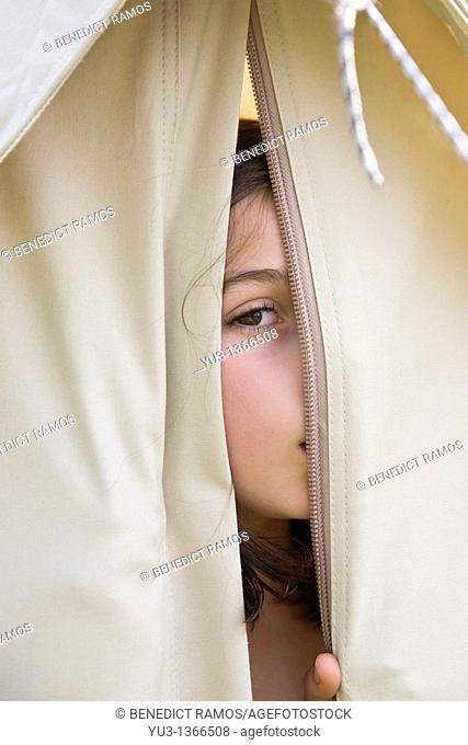 Young girl peeping through opening in a canvas tent