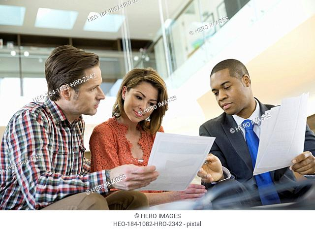 Couple reviewing paperwork with financial advisor