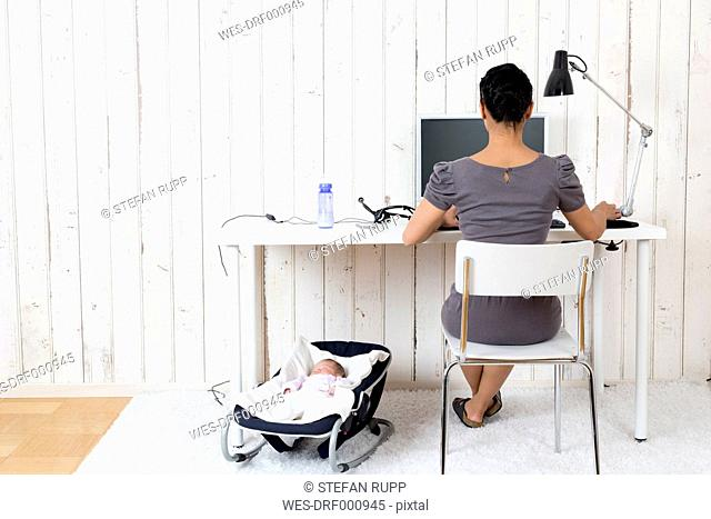 Woman working at home office while her baby lying in bouncy seat