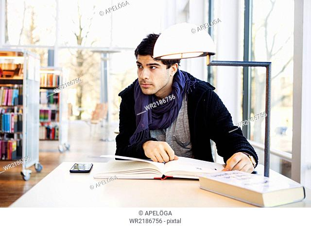 Young man with books at table in library