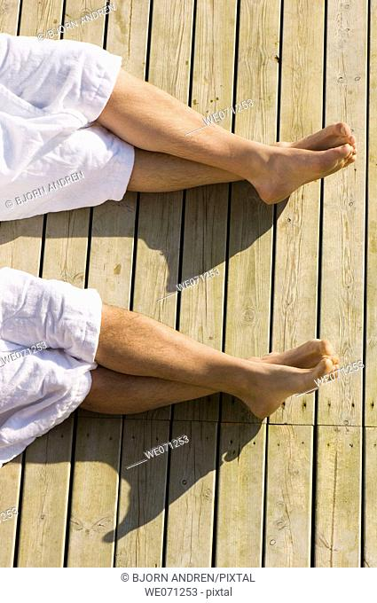 Four legs and feet with white bathrobes on wooden boardwalk