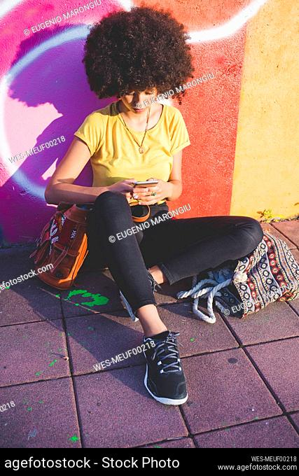 Young woman with afro hairdo sitting at graffiti wall and using smartphone