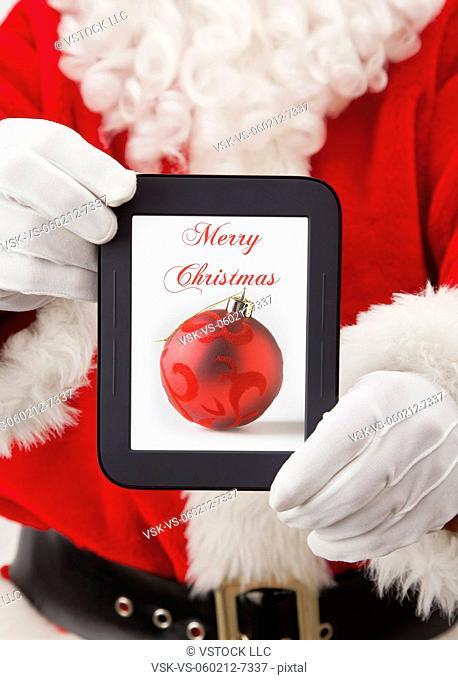 USA, Illinois, Metamora, Santa claus holding digital tablet with christmas decoration on screen