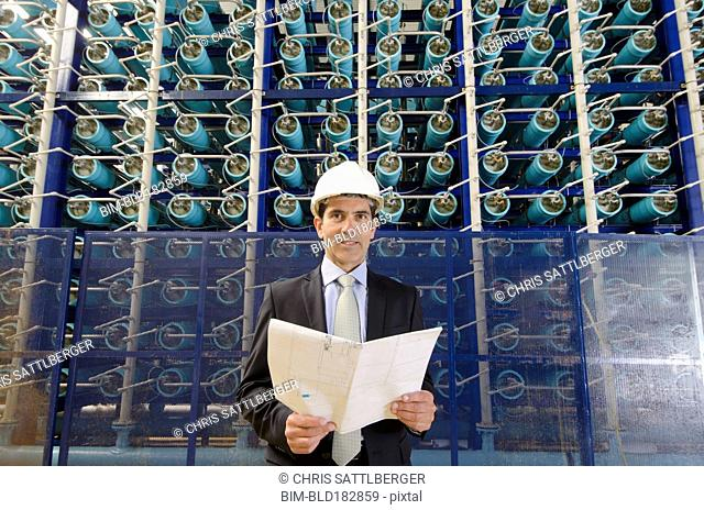 Hispanic businessman smiling in power plant