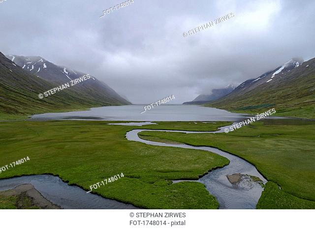 Scenic view of fjord amidst mountains against cloudy sky, Iceland