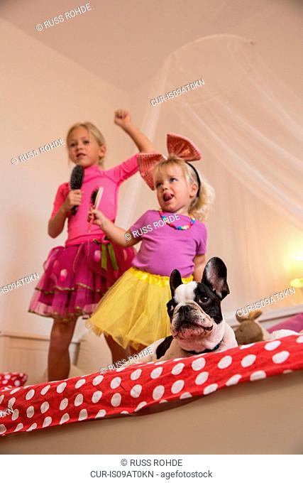 Girl and toddler sister dancing and singing with microphone and hairbrush on bed