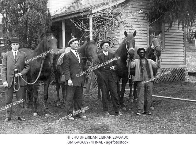 Full length standing portraits of three white men and one African American man with four horses, three white men wearing dark suits, ties and hats