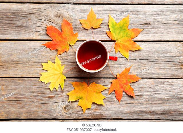 Autumn leafs with cup of tea on grey wooden table