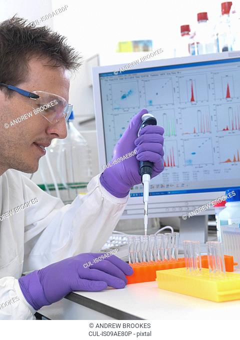 Male scientist pipetting sample into test tubes for analysis of cell population