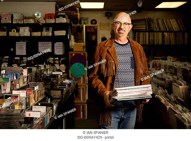 Portrait of mature man in record shop, holding records