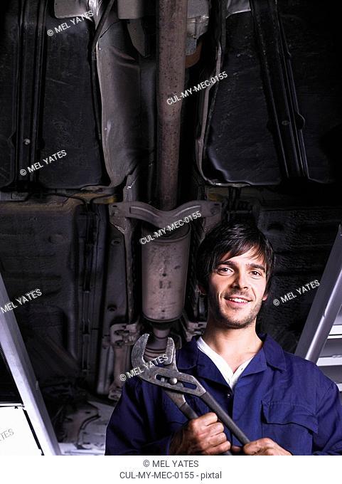 Mechanic under a raised car