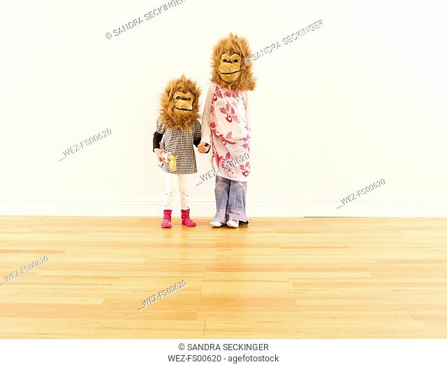 Two girls wearing monkey masks standing hand in hand in front of white wall
