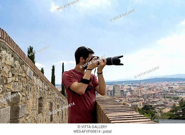 Spain, Girona, man at the castletaking picture of the city