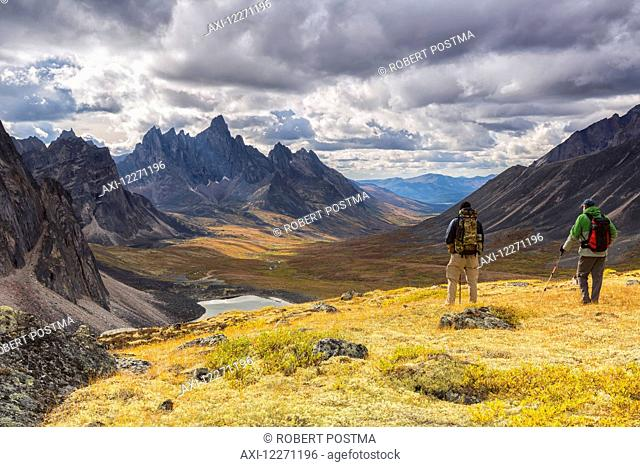 Hikers on an overlook viewing the beautiful autumn colours in Tombstone Territorial Park, with Tombstone Mountain in the distance; Yukon, Canada