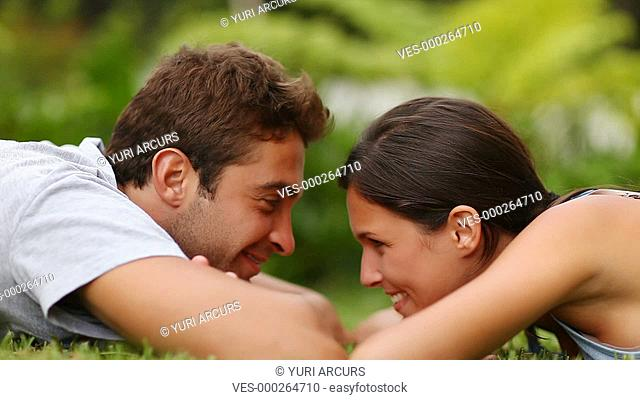 Cute young couple lying on the grass and sharing a loving moment