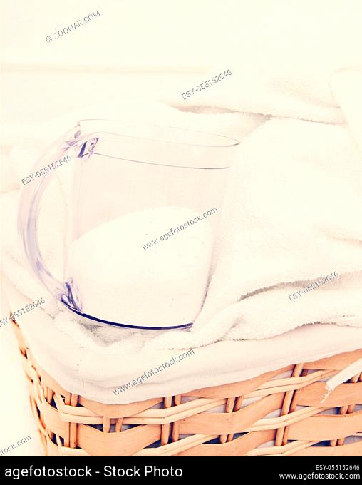 Laundry. Wicker basket with dirty towels and powder