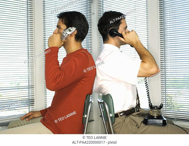Two men sitting back to back, one with cell phone, other with rotary telephone