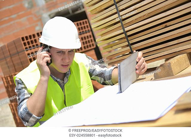 Foreman using walkie-talkie and digital tablet on construction site, France