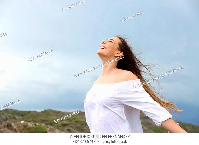 Positive woman breathing fresh air enjoying the wind