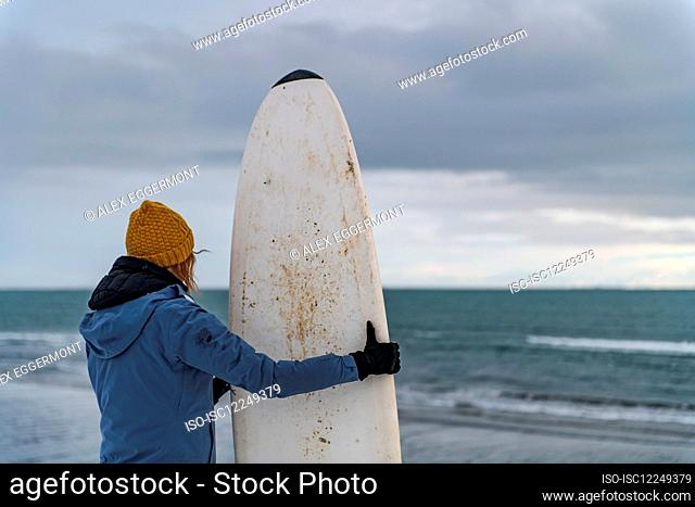 Rear view of a woman holding a surfboard standing on a snowy beach and looking out to sea