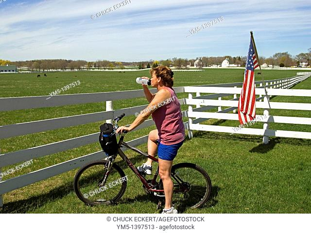 Girl on bicycle drinking water during rest stop