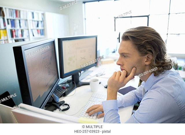 Focused architect working at computer in office