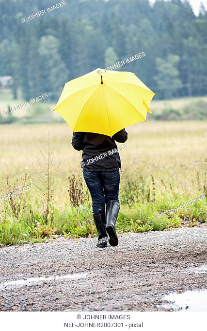 Woman with yellow umbrella, rear view